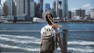 Camera follows young happy traveler girl with backpack, jumping with arms wide open at Manhattan skyline in New York.