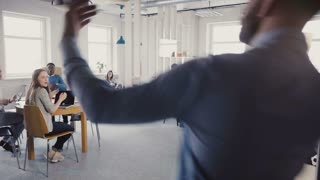 Camera follows young man enter office with crazy victory dance, celebrate success. Multi-ethnic colleagues clapping 4K.