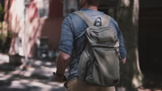 Camera follows young relaxed local man with backpack walking along shady summer Brooklyn street in New York slow motion.