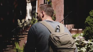 Camera follows young relaxed tourist man with backpack walking along shady summer New York city street with coffee.