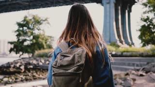 Camera follows young traveler girl with backpack walking along beautiful sunny Brooklyn Park river bank slow motion.
