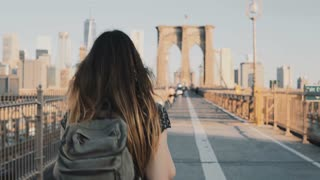 Camera follows young woman with backpack walking along Brooklyn Bridge, New York on a beautiful sunny summer day 4K.