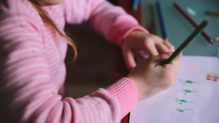 Camera sliding right over cute Caucasian little girl drawing on paper with different color pencils at a table close-up.