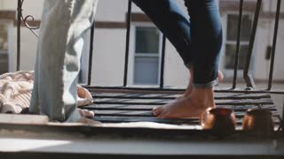 Camera tilts up to reveal happy romantic man and woman standing barefoot together at beautiful morning Brooklyn balcony.