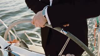 Captain of the ship standing behind steering wheel. Young businessman driving the yacht in bright sunny day.