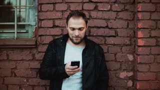 Casual Caucasian man using smartphone outside. Handsome bearded young male businessman texting. Red brick wall 4K.