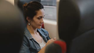 Casual female passenger on the train sits in a comfortable seat using smartphone e-commerce app, looking at the window.
