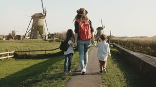 Casual mother with two kids near windmill farm. Woman in hat with red backpack, little boy and girl walking together. 4K