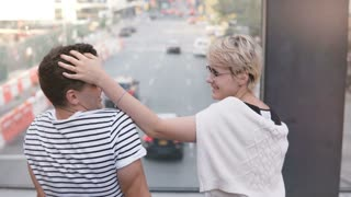 Casual young multiethnic couple sitting on a bridge over New York street having fun, smiling and trying eyeglasses on.
