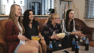 Caucasian female friends watch popular TV show. Happy smiling girls watch funny action film at home 4K slow motion.