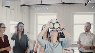 Caucasian girl juggles football on head in office. Happy multiracial business people celebrate work success clapping 4K.