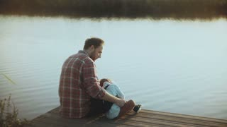 Caucasian man with little boy sit on a lake pier. Father and son together. Happy relationship. Bringing up children. 4K.