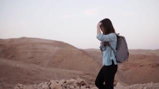 Caucasian woman hiking in desert. Slow motion. Tourist girl wanders on desert canyon edge smiling happy. Israel summer.
