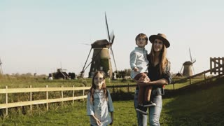 Caucasian woman with two kids near a windmill farm. Mother, little boy and cute girl explore surroundings together. 4K.