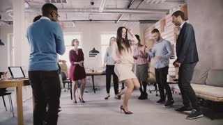 Cheerful businesswoman dancing at casual office teambuilding party. Multiethnic team share fun time together slow motion