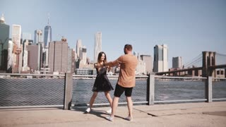 Cheerful European couple do a happy spin dance near famous New York skyline view at Manhattan, hold hands slow motion.