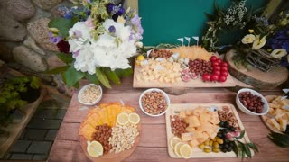 Cheese table with other snacks outside. Flowers, slices cheese, nuts, eggs, drinks and tomatoes. Top view.