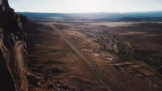 Cinematic aerial view of epic wide open desert wilderness of Arizona endless desert valley with car moving along highway
