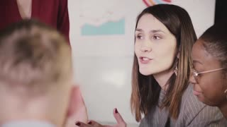 Close-up of successful confident businesswoman talking to multiethnic workers at company team training seminar session.