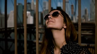 Close-up portrait of happy Caucasian woman in sunglasses looking in the sky, enjoying sunny day at Brooklyn Bridge 4K.