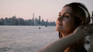Close-up portrait of young beautiful European girl looking at sunset, then posing at camera near big city river 4K.