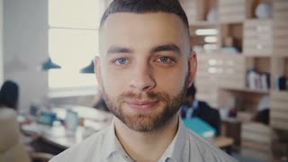 Close-up portrait of young European successful entrepreneur looking at camera in office, changing face expression 4K.