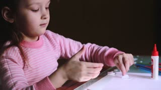 Close-up shot of beautiful little preschool European girl child in pink sweater sitting by the table gluing paper shapes