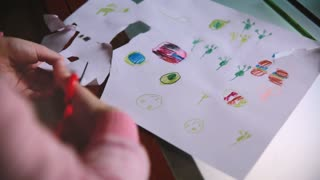 Close-up shot of cute little girl's hands cutting handdrawn pictures out from a paper sheet with scissors at a table.