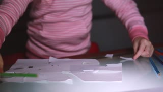 Close-up shot of little girl's hands in pink sweater cutting paper sheet shapes with scissors on a glass table.