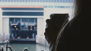 Close-up silhouette of young happy female tourist with coffee on a ferry coming up to the dock on a cold foggy morning.