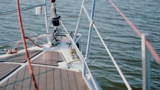 Close-up vie of nasal part of sailboat goes through the water. Sailing in wind in sunny day in open sea.