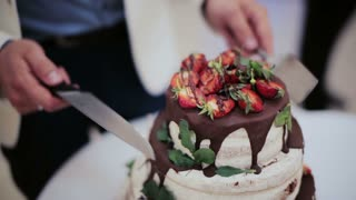 Close up view of a bride and groom cutting their wedding cake in the style of boho with chocolate and fresh berries.
