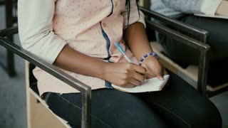 Close-up view of african female hands. Woman sitting on a chair and writing in notebook. Student girl at a lecture.