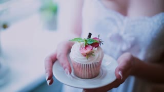 Close-up view of beautiful cupcake on a saucer. Woman holds a plate with cake, the smells the dessert.