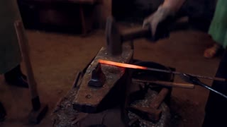 Close-up view of blacksmith working with hammer and hot red metal. Man forge the iron on the anvil in smithy.