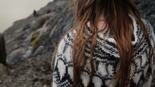 Close-up view of brunette female hair waving on the wind. Young woman in lopapeysa sweater hiking in the mountains.