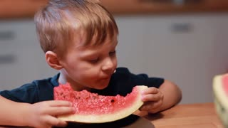 Close-up view of cute little boy sitting at the table on the kitchen. Child holding a piece and eating a watermelon.