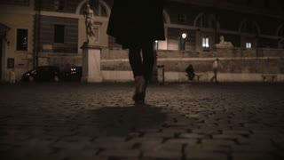 Close-up view of female feet walking through the deserted street in the evening. Lonely woman going home late.