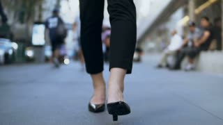 Close-up view of female feet walking through the downtown. Businesswoman wearing shoes with heels. Slow motion.