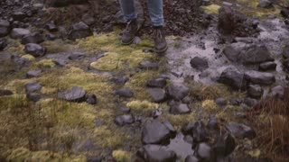 Close-up view of female foot in boots. Young woman walking through the bogs with moss, exploring the nature alone.