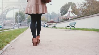 Close-up view of female foot. Young stylish woman walking near the Eiffel tower in Paris, France early in the morning.