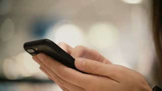 Close-up view of female hands holding smartphone, using the touchscreen technology. Young woman typing on the screen.