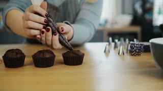 Close-up view of female hands puts the cream from pastry bag on chocolate cupcakes. Young woman cooking the muffins.