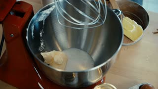 Close-up view of female hands turns on the mixer and mixing the butter with sugar for baking. Female doing hobby.