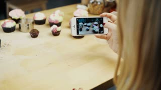 Close-up view of female taking photos of cupcakes with she has baked. Young woman using the camera on smartphone.