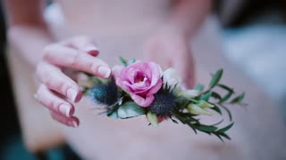 Close-up view of florist woman holding the flower composition in her hand. Girl touching the beautiful buttonhole.