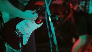 Close-up view of guitarist plays on stage. Concert rock band in a nightclub or prom. Man uses a musical instrument.