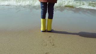 Close-up view of little girl foot in bright yellow rubber boots. Child standing on shore of beach, footprints in sand.