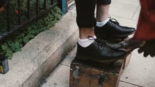 Close-up view of male, businessman feet on a stand. Shoe shiner working on the street, polishing the black shoes.