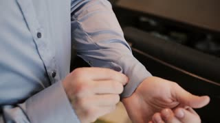 Close-up view of male hands buttons a shirt. Man clasping cuffs on a shirt. Businessman getting ready for a job.